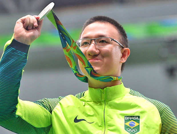 Brazil's silver medal winner Felipe Almeida Wu poses on the podium during the medal ceremony for the men's 10m air pistol shooting event at the Rio 2016 Olympic Games at the Olympic Shooting Centre in Rio de Janeiro on August 6, 2016. / AFP PHOTO / Pascal GUYOT