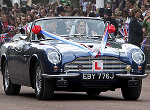 ORG XMIT: LON423 Britain's Prince William and his wife Catherine, Duchess of Cambridge drive from Buckingham Palace in an Aston Martin DB6 Mark 2, after their wedding in Westminster Abbey, in central London April 29, 2011. Prince William married his fiancee, Kate Middleton, in Westminster Abbey on Friday (ROYAL WEDDING/ BALCONY) REUTERS/Yui Mok/Pool (BRITAIN - Tags: ENTERTAINMENT SOCIETY ROYALS)
