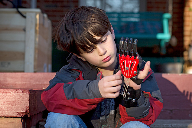 Eight-year-old Ethan Brown adjusts his Cyborg Beast 3-D printed prosthetic hand, made in his school's colors of black and red, in Opelika, Ala., Feb. 12, 2015. The proliferation of 3-D printers has had an unexpected benefit: The devices, it turns out, are perfect for creating cheap prosthetics. ÒIt looks like Ironman or Spider-Man,Ó says Brown. (Kevin Liles/The New York Times)