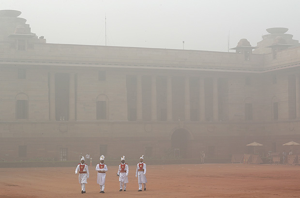 Indian presidential staff members walk surrounded by smog at the presidential palace in New Delhi, India, Tuesday, Nov. 7, 2017. Air pollution in India's capital has hit hazardous levels prompting local officials to ask that school shut down and a half marathon scheduled later in November be called off.