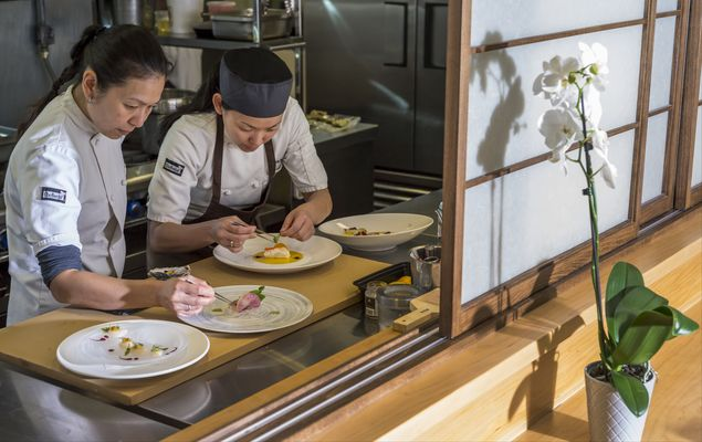 "In this Wednesday, April 15, 2015 photo, chef Niki Nakayama, left, and assistant chef Carole Lida work on plating their kaiseki menu, the traditional Japanese culinary practice at Nakayama's n/naka restaurant in Los Angeles. Nakayama is one of just six chefs to be profiled on Netflix's first homegrown documentary series, ""Chef's Table,"" which features some of the most innovative chefs cooking today. (AP Photo/Damian Dovarganes) ORG XMIT: CADD207"