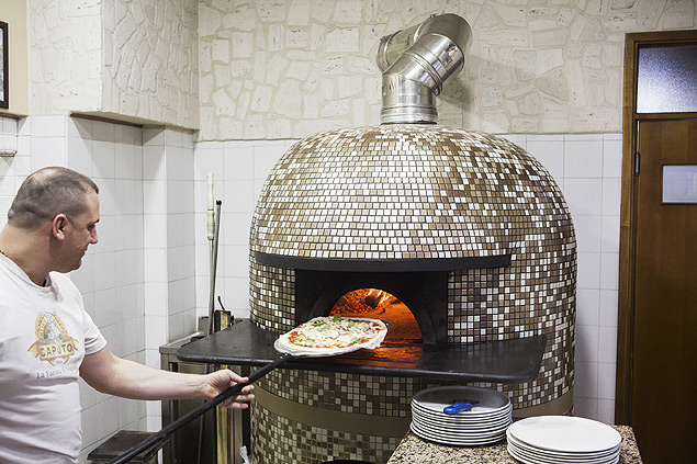 Gennaro Marano slides a pizza into the wood-fired oven at Il Cavallino in San Vitaliano, Italy, Jan. 4th 2016. Outrage was guaranteed when San Vitaliano's mayor, Antonio Falcone, issued an ordinance banning the use of wood-fired stoves and fireplaces not equipped with pollutant-reducing filters, most pointedly affecting wood-burning pizzerias. �I became the anti-pizza mayor,� he says. �I am responsible for the health of the citizens of this town. We had to start somewhere.� (Gianni Cipriano/The New York Times)