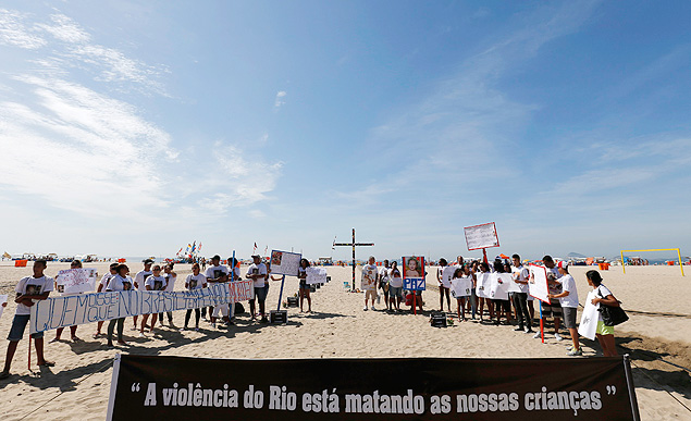 Demonstrators protest next to a cross fixed by NGO Rio de Paz, in memory of children who died in recent violence episodes, on Copacabana beach, in Rio de Janeiro