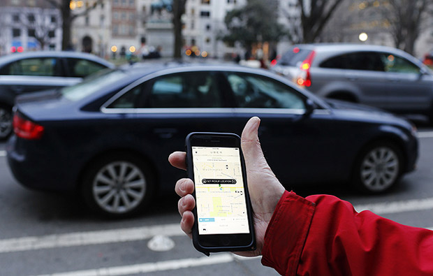 o: (FILES) This March 25, 2015 file photo shows an UBER application viewed as cars drive by in Washington, DC. They drive for Uber, deliver groceries for Instacart, run errands for TaskRabbit, and rent their spare rooms on Airbnb. Are these the new, empowered participants in the