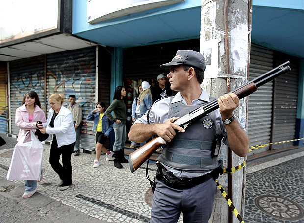 A policeman guards a commercial area in the suburbs of São Paulo, Brazil