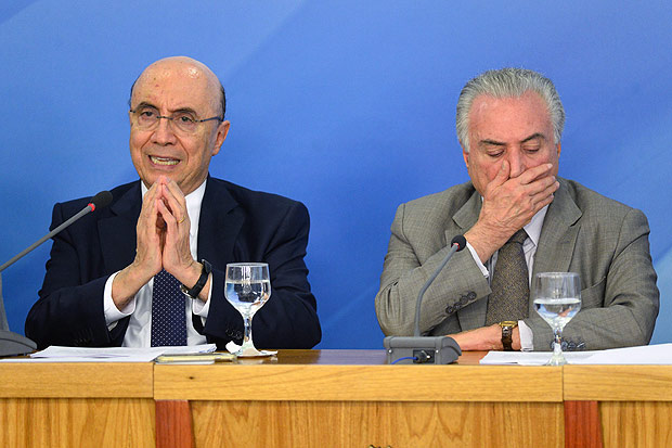 Brazilian President Michel Temer (R) and Finance Minister Henrique Meirelles (L) announce new measures to stimulate the economy, in the Planalto Palace on December 15, 2016 in Brasilia. / AFP PHOTO / ANDRESSA ANHOLETE