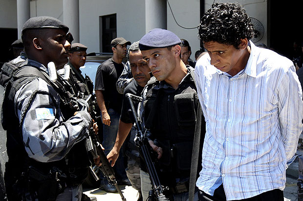 "Antonio Bonfim Lopes or ""Nem,"" the alleged drug lord of the teeming Rocinha slum, is escorted by policemen at the federal police headquarters in Rio de Janeiro, November 10, 2011"