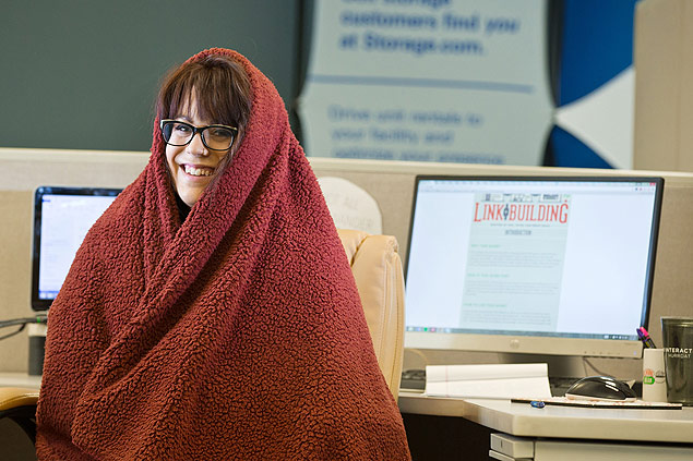 Molly Mahannah wearing a sweatshirt and a blanket at her desk at B2 Interactive, a web design and digital marketing agency, in Omaha, Neb., July 31, 2015. Most office buildings set temperature based on a formula from the '60s based on the metabolic rates of men. This formula is now being challenged to reduce energy consumption and combat global warming. (Chris Machian/The New York Times) - XNYT36