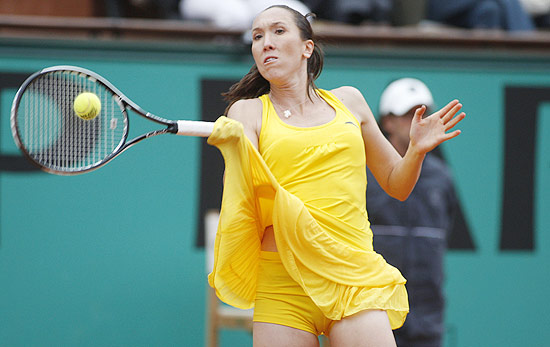 Serbia's Jelena Jankovic's outfit becomes entangled in her racket as she returns the ball to Estonia's Kaia Kanepi during a second round match of the French Open tennis tournament at the Roland Garros stadium in Paris, Thursday, May 27, 2010. (AP Photo/Michel Euler)