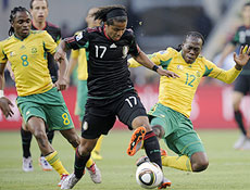 South Africa's Reneilwe Letsholonyane, right, tackles Mexico's Giovani Dos Santos, center, as South Africa's Katlego Mphela looks at them during the World Cup group A soccer match between South Africa and Mexico at Soccer City in Johannesburg, South Africa, on Friday, June 11, 2010. (AP Photo/Martin Meissner)