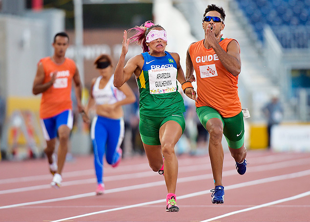 Guilher Aparecida, left, and her guide Guilherme Santana De Soares, of Brazil, compete in the women's 100-meter T11 final during the Parapan American Games in Toronto on Tuesday, Aug. 11, 2015. Aparecida won gold. (Nathan Denette/The Canadian Press via AP) ORG XMIT: NSD109