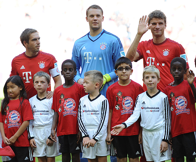 Back row from left: Munich players Philipp Lahm, goal keeper Manuel Neuer and Thomas Mueller pose with migrant and refugee children before the German Bundesliga soccer match between FC Bayern Munich and FC Augsburg at the Allianz Arena in Munich, Germany, Saturday Sept. 12, 2015. (Andreas Gebert/dpa via AP) ORG XMIT: MFRA102