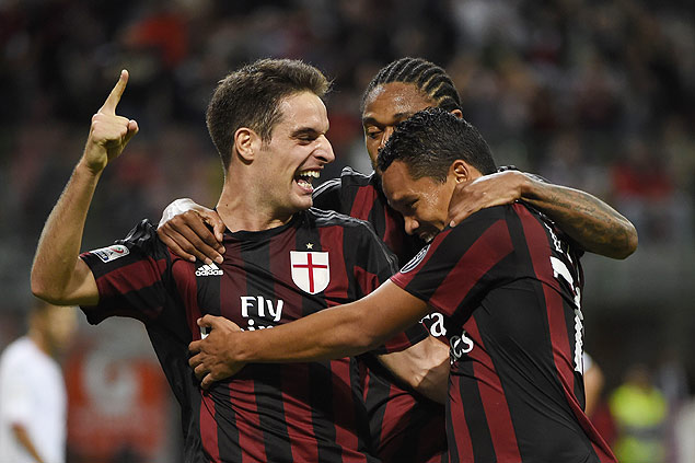 AC Milan's Colombian forward Carlos Bacca (R) celebrates with his teammates Italian midfielder Giacomo Bonaventura after scoring during the Italian Serie A football match AC Milan vs Palermo on September 19, 2015 at the San Siro Stadium stadium in Milan. AFP PHOTO / OLIVIER MORIN ORG XMIT: OLM1396