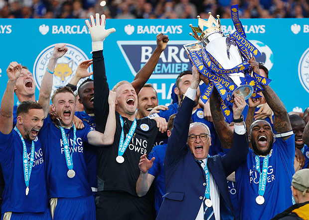 Leicester City's Italian manager Claudio Ranieri (2R) and Leicester City's English defender Wes Morgan hold up the Premier league trophy after winning the English Premier League football match between Leicester City and Everton at King Power Stadium in Leicester, central England on May 7, 2016. / AFP PHOTO / ADRIAN DENNIS / RESTRICTED TO EDITORIAL USE. No use with unauthorized audio, video, data, fixture lists, club/league logos or 'live' services. Online in-match use limited to 75 images, no video emulation. No use in betting, games or single club/league/player publications. /