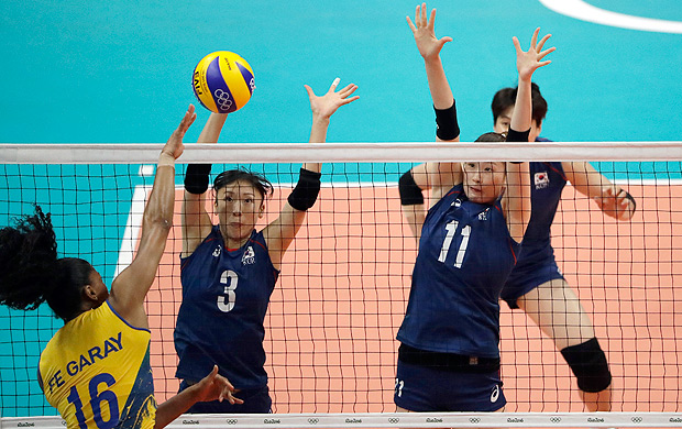 South Korea's Lee Hyo-hee (3) and Kim Su-ji (11) block as Brazil's Fernanda Rodrigues spikes the ball during a women's preliminary volleyball match at the 2016 Summer Olympics in Rio de Janeiro, Brazil, Friday, Aug. 12, 2016. (AP Photo/Matt Rourke) ORG XMIT: OVOL248