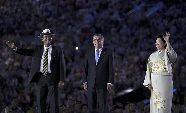2016 Rio Olympics - Closing ceremony - Maracana - Rio de Janeiro, Brazil - 21/08/2016. Rio de Janeiro mayor Eduardo Paes, International Olympic Committee President Thomas Bach (L) and Tokyo governor Yuriko Koike wave on stage. REUTERS/Stefan Wermuth FOR EDITORIAL USE ONLY. NOT FOR SALE FOR MARKETING OR ADVERTISING CAMPAIGNS. ORG XMIT: OLYGK81