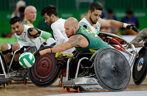 Australia's Ryley Batt controls the ball under pressure from Brazil's Julio Braz, behind right, during a mixed wheelchair rugby group A game at the Paralympic Games in Rio de Janeiro, Brazil, Thursday, Sept. 15, 2016. (AP Photo/Leo Correa) ORG XMIT: XLC120