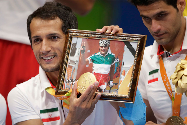2016 Rio Paralympics - Sitting Volleyball - Victory Ceremony - Men's Gold Medal Match - Riocentro Pavilion 6 - Rio de Janeiro, Brazil - 18/09/2016. Ramezan Salehihajikolaei (IRI) of Iran holds his gold medal and a photograph of Iranian cyclist Sarafraz Bahman Golbarnezhad, during the medal ceremony. REUTERS/Ueslei Marcelino FOR EDITORIAL USE ONLY. NOT FOR SALE FOR MARKETING OR ADVERTISING CAMPAIGNS. ORG XMIT: CDG49