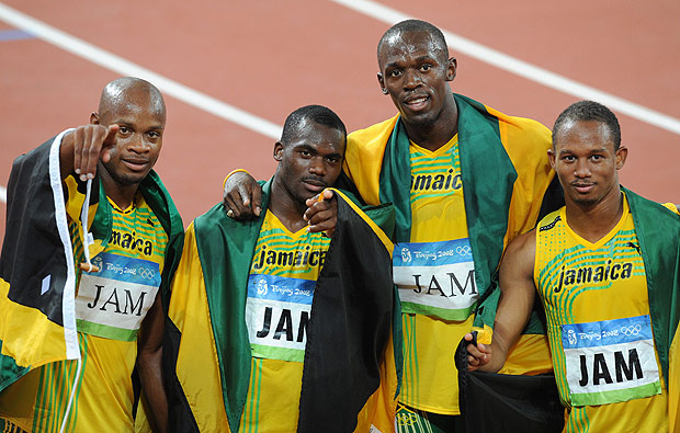 (FILES) This file photo taken on August 22, 2008 shows (from front, L) Jamaica's Asafa Powell, Nesta Carter, Usain Bolt and Michael Frater celebrating after winning the men's 4×100m Relay final at the National Stadium during the 2008 Beijing Olympic Games. The International Olympic Committee said on January 25, 2017 it had stripped Jamaica of their gold medal earned in the 4x100m relay at the 2008 Beijing Games after Nesta Carter was caught doping. The decision which follows the retesting of hundreds of samples from the Beijing event, means teammate Usain Bolt loses one of the three gold medals he won at that Olympics. Carter was found to have tested positive for banned substance Methylhexanamine. / AFP PHOTO / WILLIAM WEST ORG XMIT: SD2005