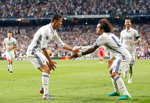 Real Madrid's Cristiano Ronaldo, left, celebrates with Marcelo after scoring his side's third goal during the Champions League quarterfinal second leg soccer match between Real Madrid and Bayern Munich at Santiago Bernabeu stadium in Madrid, Spain, Tuesday April 18, 2017. (AP Photo/Daniel Ochoa de Olza) ORG XMIT: XAF169