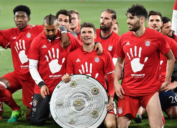 Bayern's team celebrates with a mock-trophy becoming the new German champion after the German first division Bundesliga football match between VfL Wolfsburg and Bayern Munich on April 29, 2017 in Wolfsburg, northern Germany. Bayern Munich won a fifth consecutive German league title. / AFP PHOTO / John MACDOUGALL / RESTRICTIONS: DURING MATCH TIME: DFL RULES TO LIMIT THE ONLINE USAGE TO 15 PICTURES PER MATCH AND FORBID IMAGE SEQUENCES TO SIMULATE VIDEO. == RESTRICTED TO EDITORIAL USE == FOR FURTHER QUERIES PLEASE CONTACT DFL DIRECTLY AT + 49 69 650050