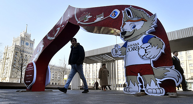 A man walks through a Confederations Cup 2017-themed arch decorated with an image of Zabivaka, the mascot for the 2018 World Cup, in central Moscow on March 14, 2017. / AFP PHOTO / Yuri KADOBNOV