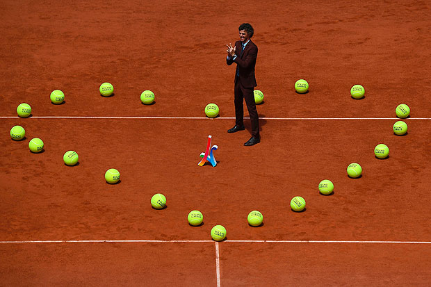 TOPSHOT - Brazilian former tennis player Gustavo Kuerten poses in the middle of the heart shaped with tennis balls before men's final tennis match at the Roland Garros 2017 French Open on June 11, 2017 in Paris. / AFP PHOTO / GABRIEL BOUYS