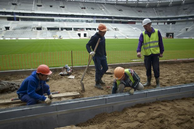FILE In this file photo taken on Wednesday, Sept. 7, 2016Workers at the Luzhniki stadium, which is undergoing a major rebuild to be ready to host the 2018 World Cup final, in Moscow, Russia. A new report by Human Rights Watch says workers building stadiums for next year's soccer World Cup in Russia have faced repeated abuses and at least 17 have died. The report says workers on several stadiums have routinely gone unpaid for several months. (AP Photo/Ivan Sekretarev, file) ORG XMIT: XAZ129
