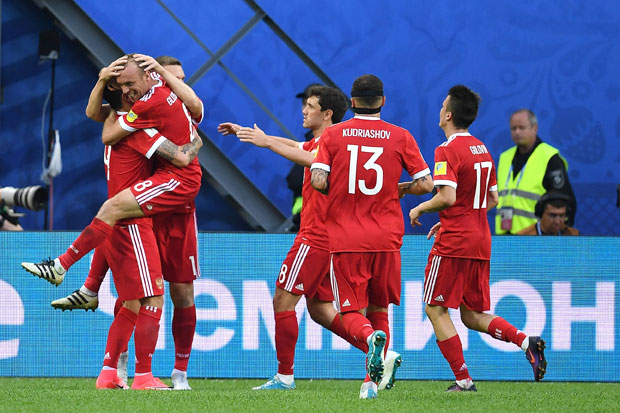 Russia's midfielder Denis Glushakov (2nd L), who scored the first goal, jumps and hugs Russia's forward Fedor Smolov, who scored the team's second goal, after Russian beat New Zealand 2-0 in the 2017 Confederations Cup group A football match between Russia and New Zealand at the Krestovsky Stadium in Saint-Petersburg on June 17, 2017. / AFP PHOTO / Kirill KUDRYAVTSEV