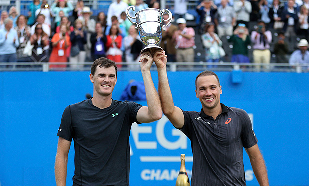 Great Britain's Jamie Murray, left, and Brazil's Bruno Soares celebrate as they hold the trophy aloft after winning their doubles match against French doubles partners Julien Benneteau and Edouard Roger-Vasselin, during the final of The Queen's Club tennis tournament, London, Sunday June 25, 2017. (Steven Paston/PA via AP) ORG XMIT: LON888