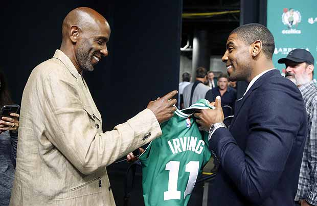 Boston Celtics' Kyrie Irving gives his father, Drederick, his Celtics jersey after a news conference in Boston, Friday, Sept. 1, 2017. (AP Photo/Winslow Townson)