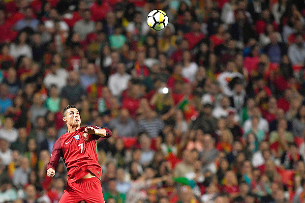 Portugal's midfielder Cristiano Ronaldo jumps for the ball during the FIFA World Cup 2018 Group B qualifier football match between Portugal and Switzerland at the Luz Stadium in Lisbon on October 10, 2017. / AFP PHOTO / FRANCISCO LEONG ORG XMIT: 3210