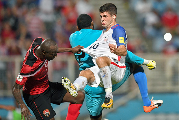 Trinidad and Tobago's Daneil Cyrus (L) and USA's Christian Pulisic vie during their 2018 World Cup qualifier football match in Couva, Trinidad and Tobago, on October 10, 2017. / AFP PHOTO / Luis ACOSTA