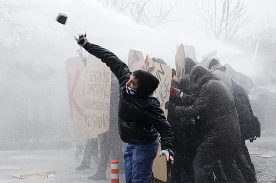 ORG XMIT: AGEN1101051219381451 ORG XMIT: IST05 A demonstrator throws a stone at police as they clash during protests against the government's education policies, at the Middle East Technical University (ODTU) in Ankara January 5, 2011. Turkish riot police used water cannons to prevent demonstrating university students from marching to the ruling Justice and Development Party headquarters. REUTERS/Umit Bektas (TURKEY - Tags: POLITICS CIVIL UNREST)