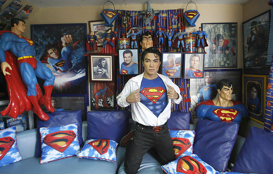 """ORG XMIT: MAN207 Herbert Chavez poses with his Superman memorabilia inside his house in Calamba Laguna, south of Manila October 12, 2011. In his idolization of the superhero, Chavez, a self-professed """"pageant trainer"""" who owns two costume stores, has undergone a series of cosmetic surgeries for his nose, cheeks, lips and chin down to his thighs and even his skin color to look more like the """"Man of Steel"""". The final result bears little resemblance to his old self. REUTERS/Cheryl Ravelo (PHILIPPINES - Tags: SOCIETY)"""