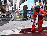 Francisco Mathurine, of the Times Square Alliance, clears snow from the steps in Father Duffy Square in New York, (Richard Drew/Associated Press)