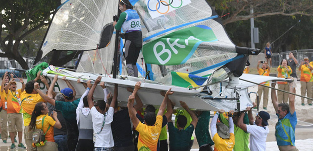 Spectators carry the boat of Brazil's Martine Grael and Brazil's Kahena Kunze out of the water after they won the 49er FX Women medal race at Marina da Gloria during the Rio 2016 Olympic Games in Rio de Janeiro on August 18, 2016.