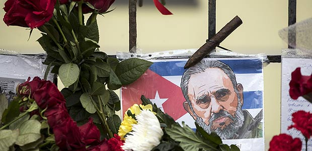 A flag with the image of revolutionary leader Che Guevara as people stay to lay flowers and candles in memory of former Cuban President Fidel Castro, who died on Friday, aged 90, at the Cuban Embassy in Moscow, Russia, Sunday, Nov. 27, 2016. Russian President Vladimir Putin said in a condolences telegram to Raul Castro, that Fidel Castro was a sincere and reliable friend of Russia. (AP Photo/Pavel Golovkin) ORG XMIT: MOSB102