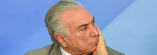 Brazilian President Michel Temer gestures during the announcement of new measures to stimulate the economy, in the Planalto Palace on December 15, 2016 in Brasilia. / AFP PHOTO / ANDRESSA ANHOLETE