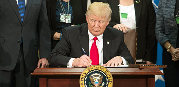 US President Donald Trump signs an executive order to start the Mexico border wall project at the Department of Homeland Security facility in Washington, DC, on January 25, 2017. / AFP PHOTO / NICHOLAS KAMM ORG XMIT: NK1713