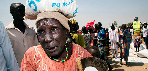 A woman carries a sack of food on March 4, 2017, in a stabilisation center in Ganyiel, Panyijiar county, in South Sudan. South Sudan was declared the site of the world's first famine in six years, affecting about 100,000 people. More than three years of conflict have disrupted farming, destroyed food stores and forced people to flee recurring attacks. Food shipments have been deliberately blocked and aid workers have been targeted. / AFP PHOTO / Albert Gonzalez Farran - AFP / Albert Gonzalez Farran