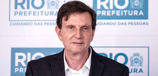 """Rio de Janeiro's Mayor Marcelo Crivella attends the unveiling ceremony of a graffiti by 19-year-old self-taught Brazilian artist Luna Buschinelli, as part of the """"Rio Big Walls"""" project in Rio de Janeiro, Brazil, on June 19, 2017. The graffiti has applied for the Guinness Book of records as the world's biggest wall painting by a female artist. / AFP PHOTO / YASUYOSHI CHIBA"""
