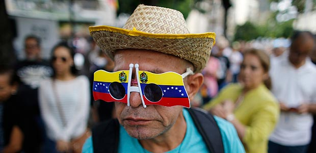A man wearing a sunglasses with the colors of the Venezuelan flag lineup prior cast his ballot at a poll station during a symbolic referendum in Caracas, Venezuela, Sunday, July 16, 2017. Venezuela's opposition called for a massive turnout Sunday in a symbolic rejection of President Nicolas Maduro's plan to rewrite the constitution, a proposal that's escalating tensions in a nation stricken by widespread shortages and more than 100 days of anti-government protests. (AP Photo/Ariana Cubillos) ORG XMIT: XFLL107