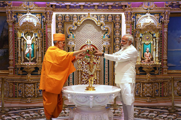 """This handout picture taken and released by on November 2, 2017, by BAPS Akshardham Temple shows Indian Head of socio-spiritual hindu organisation BAPS Mahant Swami Maharaj (L), Sadhu Keshavjivandas, and Indian Prime Minister Narendra Modi (R) performing the hindu ritual known as 'Abhishek' on an idol of Lord Swaminarayan Nilkanth Varni at Akshardham temple in Gandhinagar, some 30 kms from Ahmedabad, as Modi graced the temple's Silver Jubillee Celebrations. / AFP PHOTO / BAPS Akshardham Temple / - / RESTRICTED TO EDITORIAL USE - MANDATORY CREDIT """"AFP PHOTO / BAPS AKSHARDHAM TEMPLE"""" - NO MARKETING NO ADVERTISING CAMPAIGNS - DISTRIBUTED AS A SERVICE TO CLIENTS"""