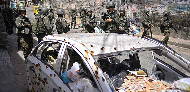 Brazilian military on patrol past an abandoned vehicle with old bullet holes in Jacarezinho favela in Rio de Janeiro