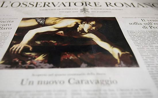 "The front page of the Vatican newspaper L'Osservatore Romano, pictured in Rome, Saturday, July 17, 2010. The newspaper has reported Saturday that a new Caravaggio painting may have been found in Rome, but cautioned that further analyses are required to ascertain whether the canvas is indeed the work of the Italian master. The front-page story in L'Osservatore Romano came out as Italy celebrates the 400th anniversary of Caravaggio's death. The painting depicts ""The Martyrdom of St. Lawrence"" and belongs to the Jesuits in Rome, the paper said. It did not say where the painting is being studied or who's examining it. An image of the painting shows a semi-naked young man amid flames, his mouth open, one arm stretched out as he leans over. (AP Photo/Gregorio Borgia)"