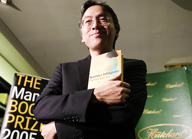 "ORG XMIT: 380801_1.tif Literatura: o escritor Kazuo Ishiguro posa com o seu livro ""Não me Abandone Jamais"", para o Booker Prize, o maior prêmio de literatura do Reino Unido, em Londres. Kazuo Ishiguro poses with his book at Hatchards book store in London, 10 October 2005, prior to the announcement of the winner of the The Man Booker Prize for Fiction. The prize is awarded every October for the best work of fiction by a British, Irish or Commonwealth author. AFP PHOTO/LEON NEAL"
