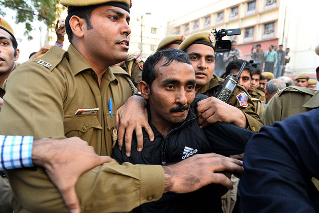 Indian police escort Uber taxi driver and accused rapist Shiv Kumar Yadav following his court appearance in New Delhi on December 8, 2014. Delhi's government on December 8 banned Uber from operating in the Indian capital after a passenger accused one of its drivers of rape, dealing a fresh blow to the reputation of online taxi service. The controversial US-based company has come in for heavy criticism in India since a young company executive said she had been raped by an Uber driver, who had previously been accused of assault. AFP PHOTO / CHANDAN KHANNA ORG XMIT: CK438