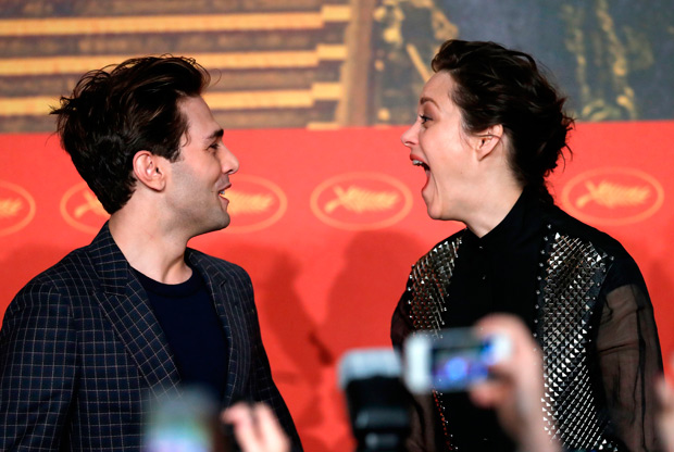 "Canadian director Xavier Dolan (L) and French actress Marion Cotillard laugh on May 19, 2016 as they arrive for a press conference for the film ""It's Only The End Of The World (Juste La Fin Du Monde)"" at the 69th Cannes Film Festival in Cannes, southern France. / AFP PHOTO / Laurent EMMANUEL"