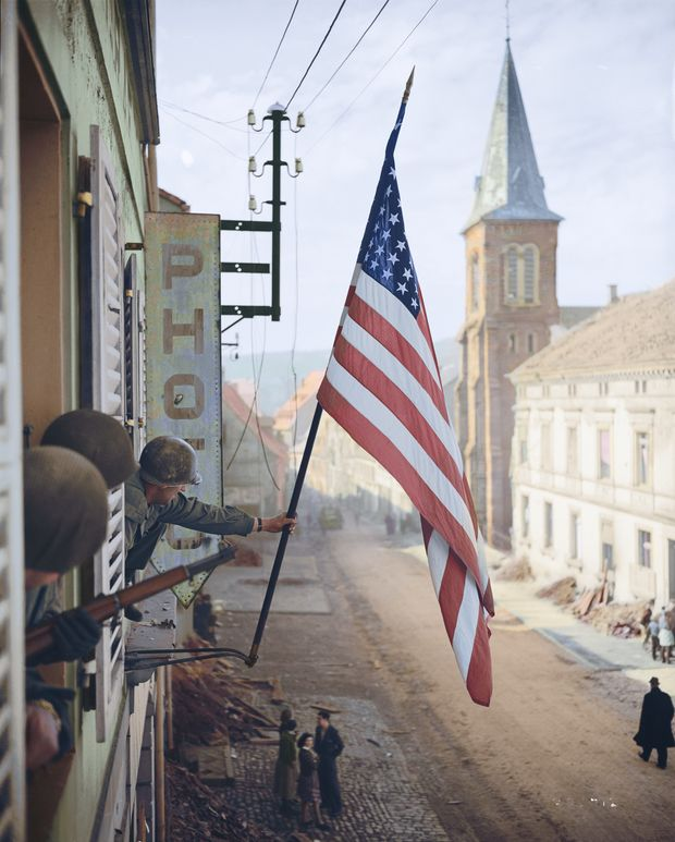 Captain Thomas H.'' Garahan Waving The American Flag After The Liberation Of The City Of Bitche (Bas-Rhin), One Of The Last Pockets Occupied By The Germans In Alsace. On March 17, 1945. Foto colorizada pela brasileira Marina Amaral.